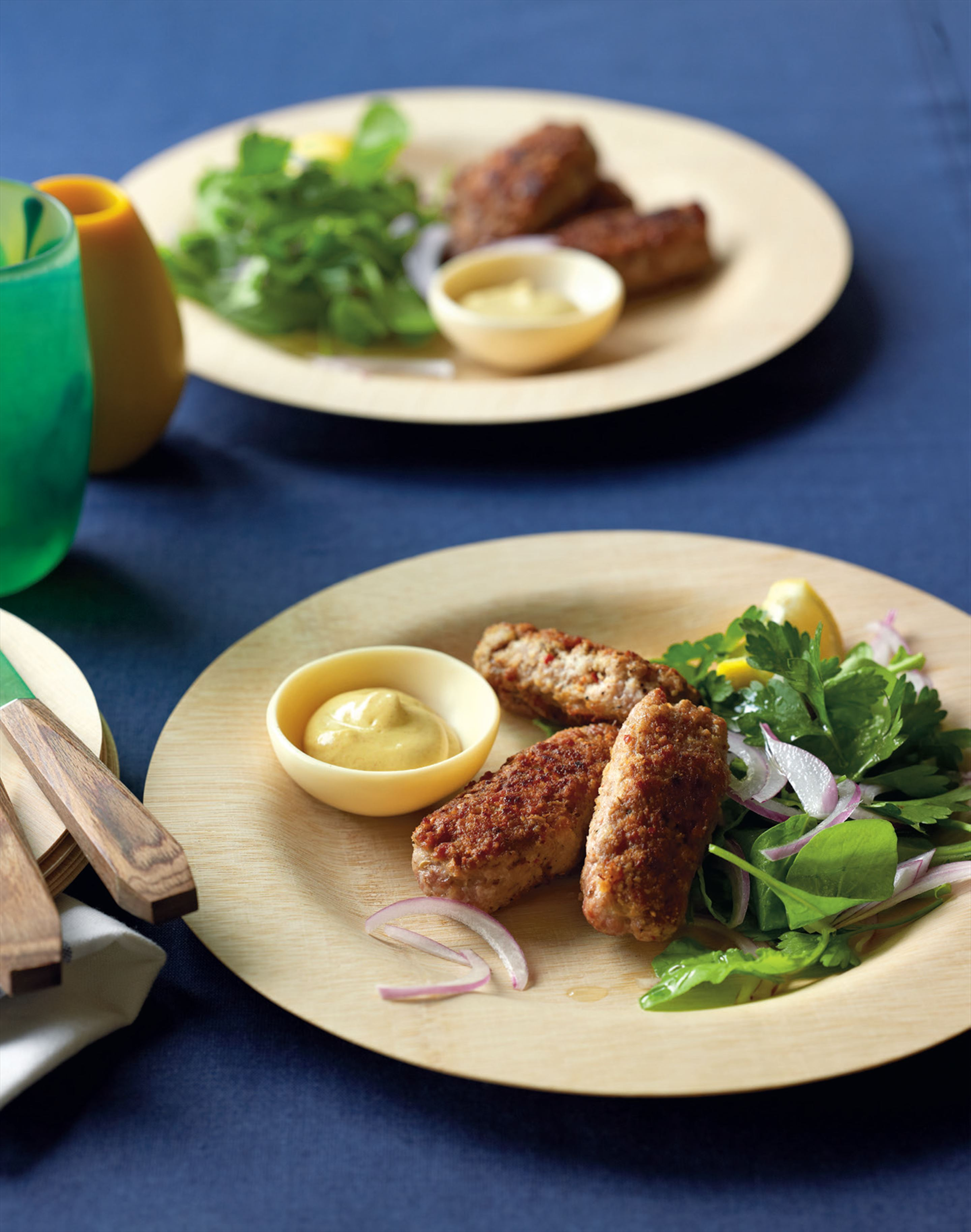 Pork cevapcici and mustard pots with rocket, parsley and red onion salad