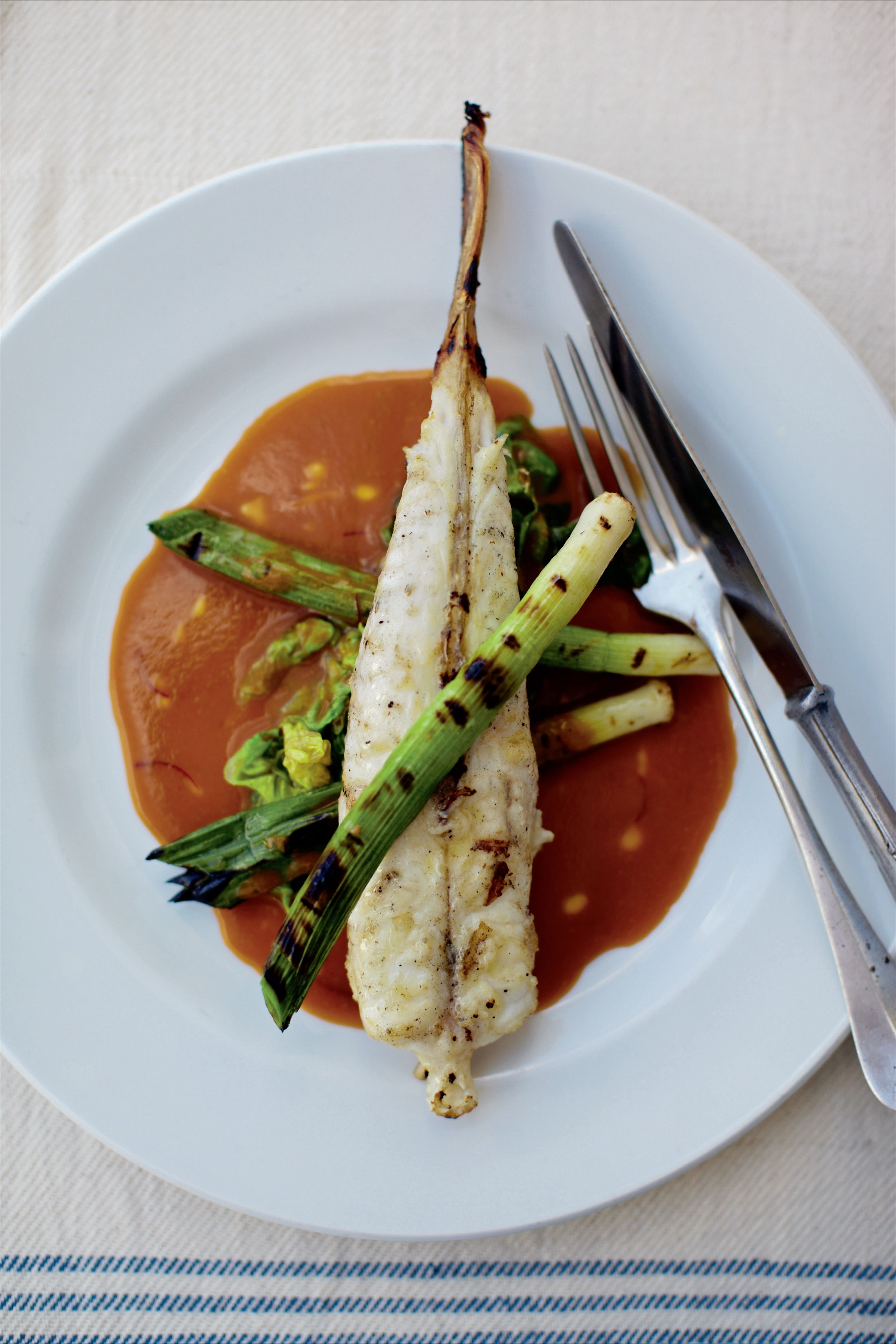 Monkfish with shellfish sauce and grilled leeks