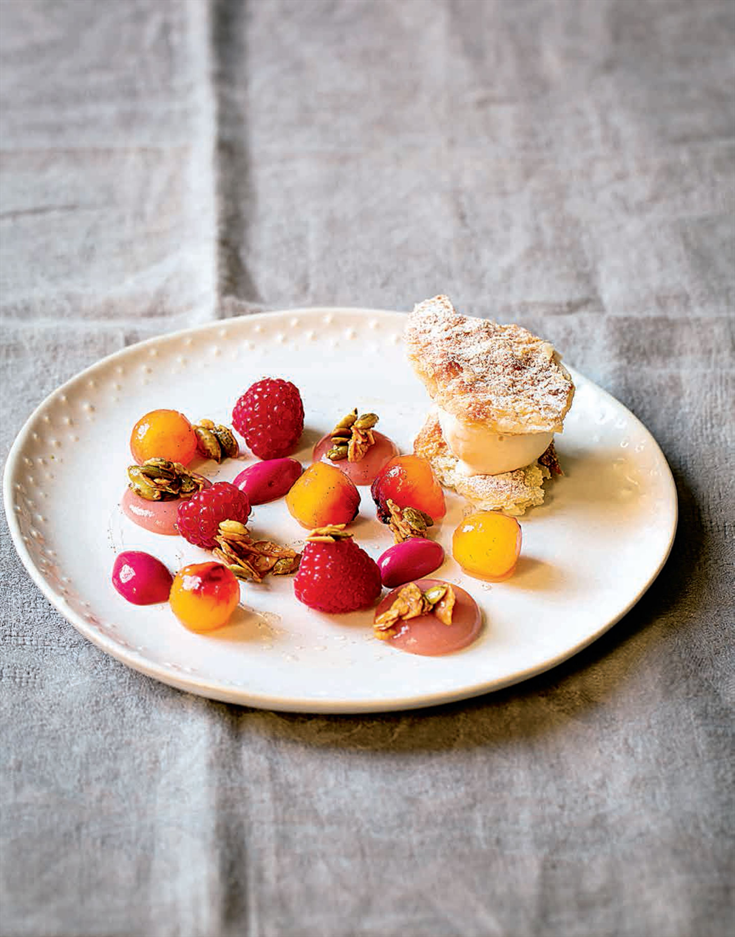 Peaches with raspberry, granola and puff pastry ice cream