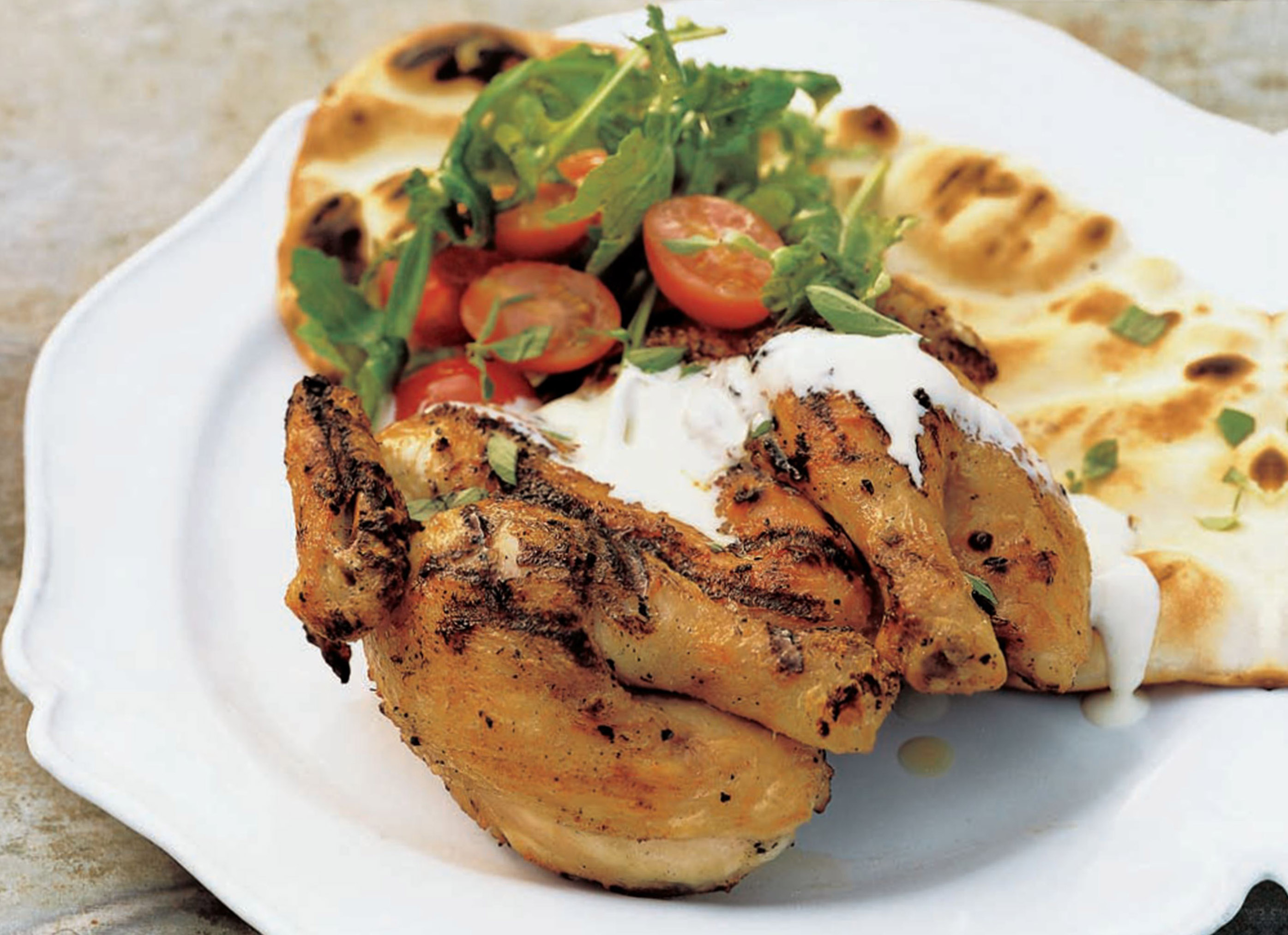 Grilled poussins with lemon, marjoram, flat bread and garlicky yoghurt