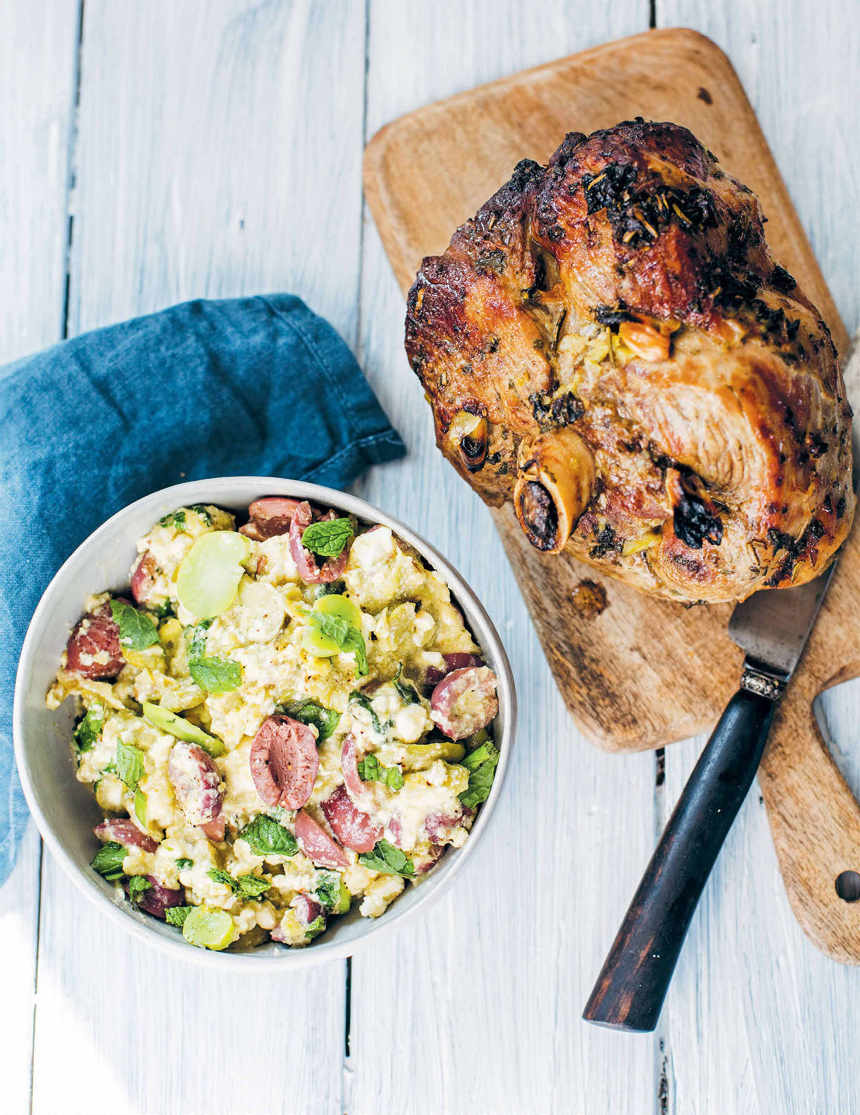 Herb-roasted leg of lamb with hot broad bean and feta dressing
