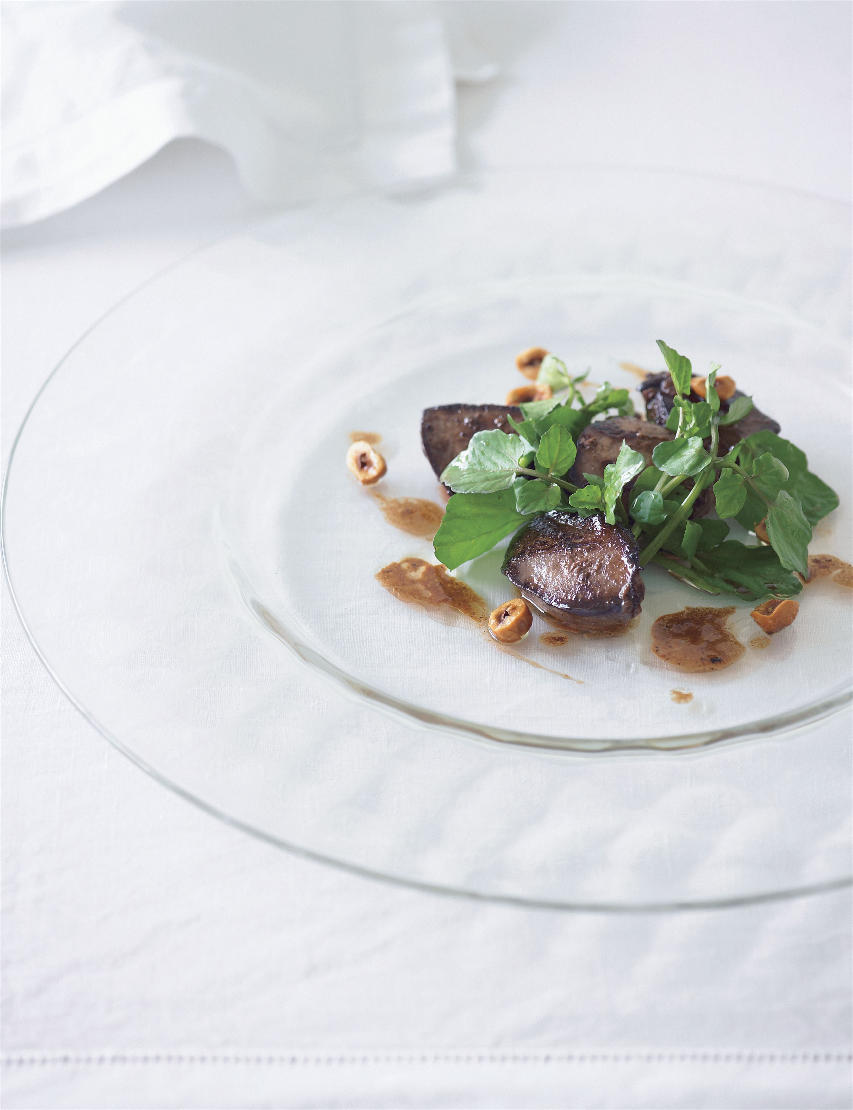 Fricassée of duck livers with watercress and roasted hazelnuts
